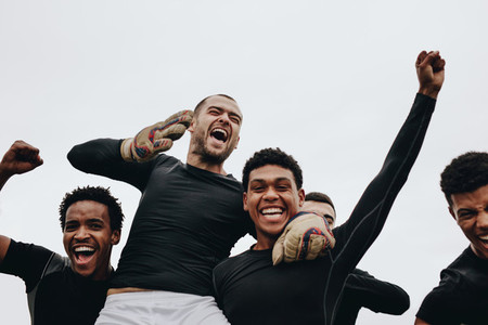 Football players screaming in joy celebrating a win