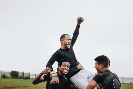 Footballers lifting the goalkeeper