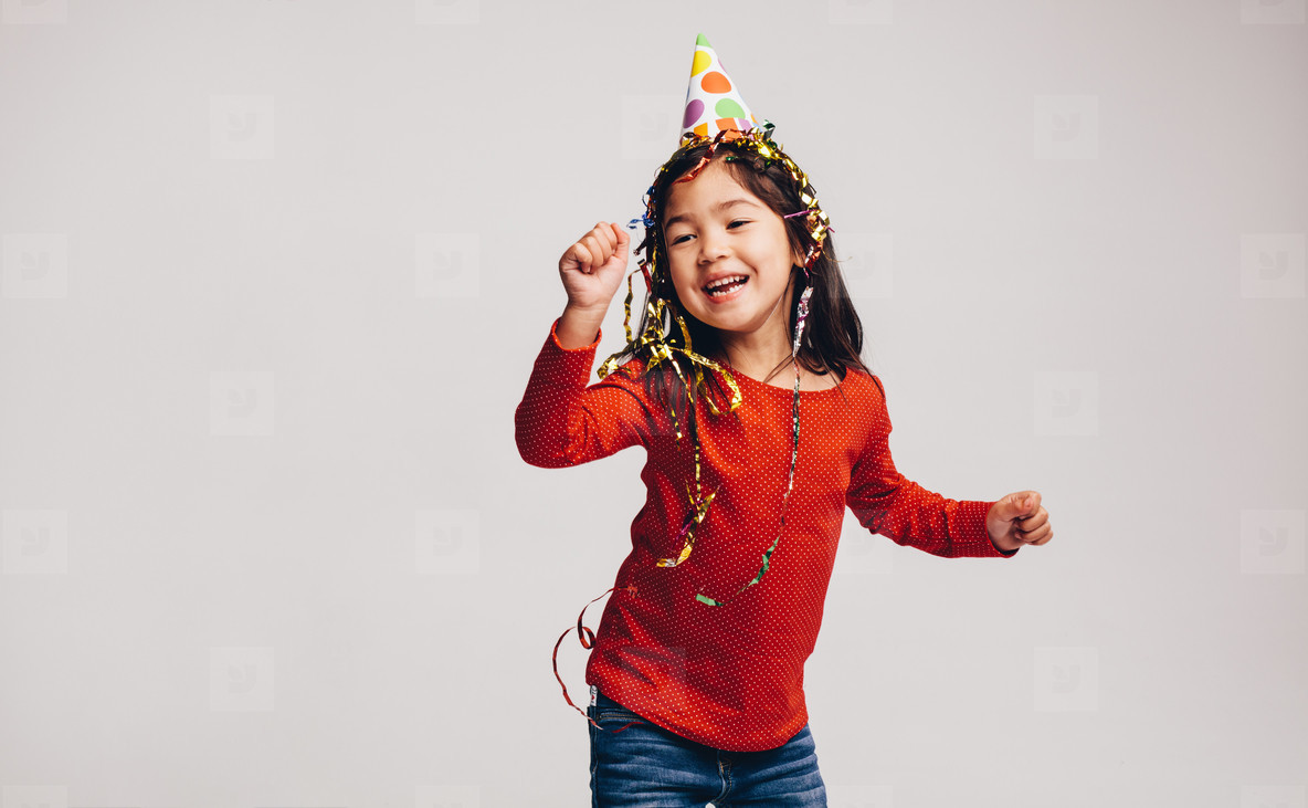 Little girl dancing wearing a party cap