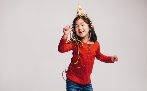 Little girl dancing wearing a party cap