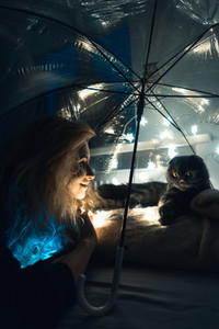 A cat and woman under an umbrella with garlands