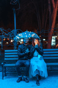 Guy and girl sitting on a bench under an umbrella