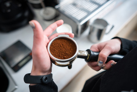 Barista holding portafilter with ground coffee