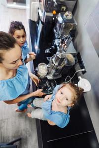 Happy family makes orange juice for breakfast