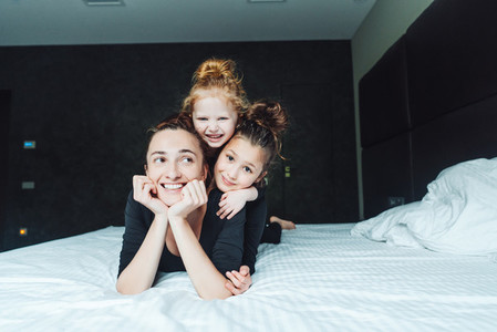 Mom and two daughters have fun on the bed