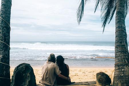 couple sitting under palm trees