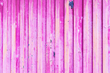 Pink rusted metal door with peeling paint