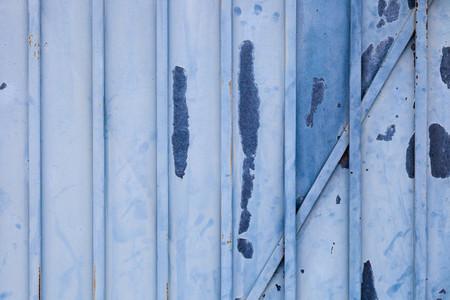 Blue rusted metal door with peeling paint