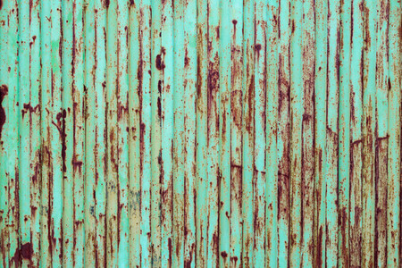 Green rusted metal door with peeling paint