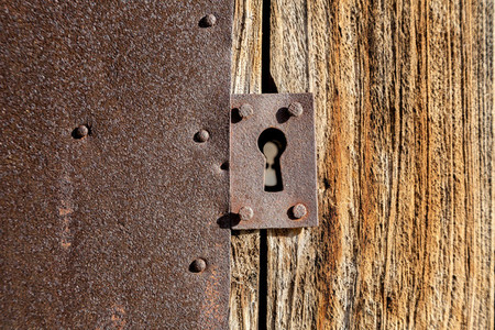 Close up antique lock on brown wooden door and rusty metallic texture