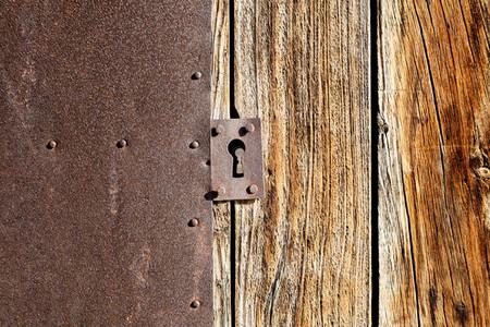 Close up antique lock on brown wooden door and rusty metallic texture