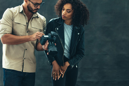 Photographer showing photos to a model on his camera