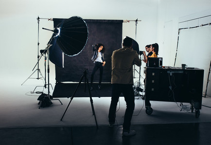 Photographer with his crew during a photo shoot in studio