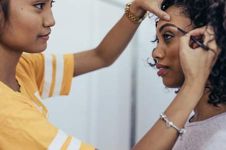 Makeup artist working on eyebrows of a model