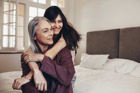 Happy women hugging her mother from behind sitting on bed
