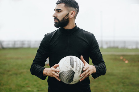 Man standing on the field holding a soccer ball