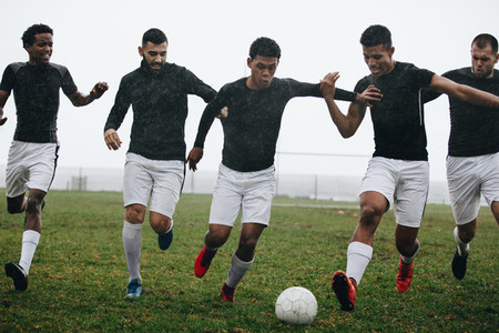 Men playing soccer in rain
