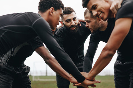 Football players in a huddle holding hands