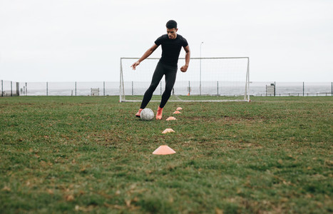 Soccer player practicing dribbling with the help of cones
