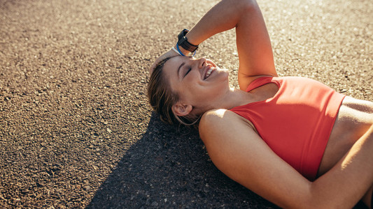 Woman athlete lying on ground relaxing during workout