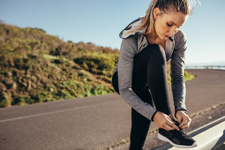 Woman runner tying her shoelace standing on road