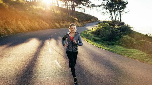Woman athlete running on road in the morning