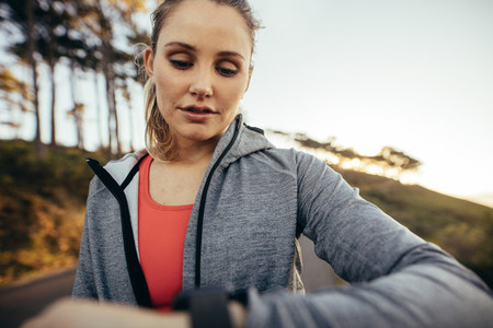Portrait of a fitness woman looking at her watch