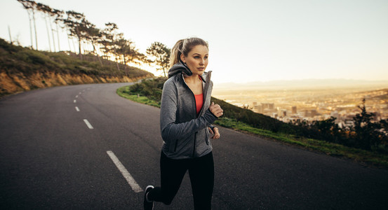 Female athlete running on road in the morning