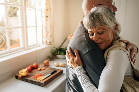 Senior man and woman embracing standing at home