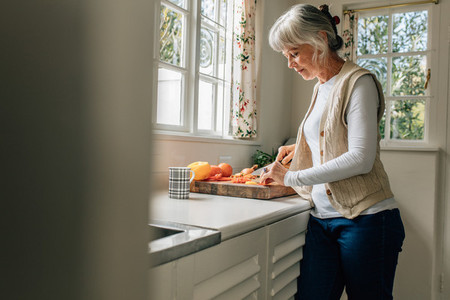 Senior woman working in kitchen at home