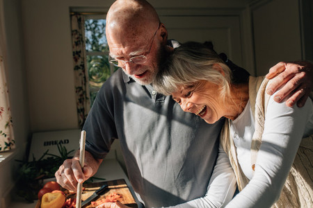 Senior couple cooking food together standing in kitchen