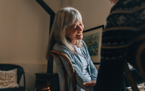 Senior woman sitting on chair at home and laughing