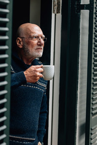 Portrait of a old man holding a coffee cup