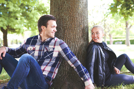 Sweet Couple at the Park Leaning Against the Tree