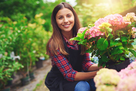 Smiling happy woman displaying a pink hydrangea