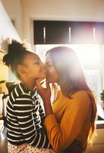 Loving mother kissing child