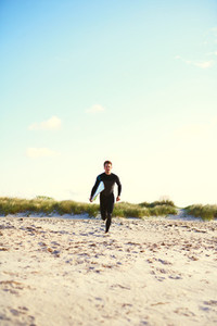 Athletic surfer running towards the surf