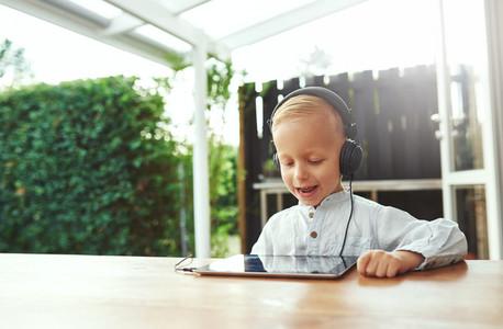 Happy vivacious little boy listening to music