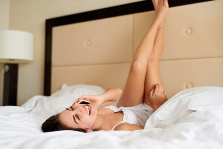 Woman lying upside down in bed talking on cell phone