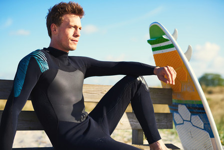 Young Surfer Sits on Bench Looking into Distance