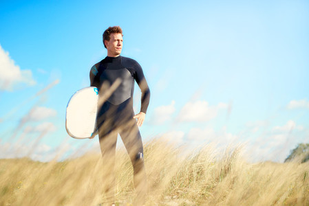 Surfer standing on a dune looking at the ocean