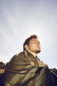 Side face of a young man with a warm scarf enjoying in calm the