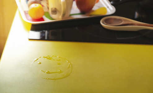 An smile drawn with water on kitchen worktop next to breakfast tray