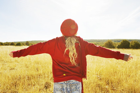 Back view of a young woman in nature in a sunny autumn day