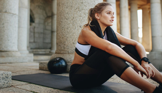 Fitness woman relaxing after workout sitting on yoga mat