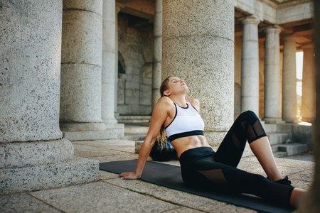 Woman in fitness wear relaxing on a yoga mat