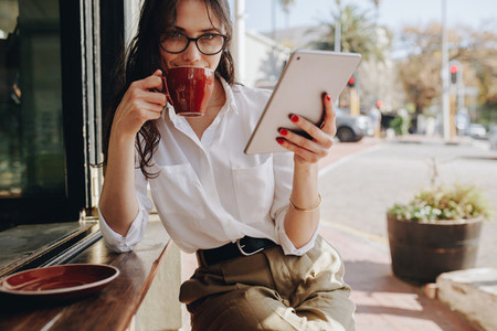 Businesswoman drinking coffee at cafe