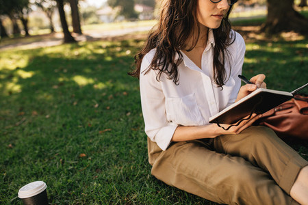 Woman relaxing at park and writing in book