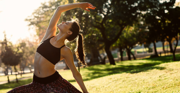 Healthy woman doing yoga stretches at the park