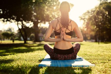 Woman doing Pashchima Namaskarasana yoga at park